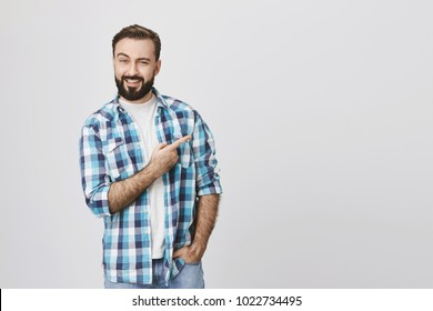 Portrait of handsome confident person with beard, lifting one eyebrow and smiling while pointing right, wearing casual clothes and standing against gray background. Man offers to check out new bar