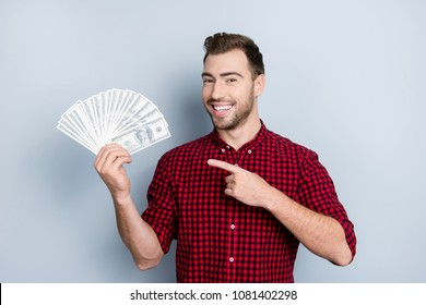 Portrait of handsome confident with toothy beaming smile smart rich wealthy friendly cheerful excited entrepreneur demonstrating many banknotes in hand with forefinger isolated on gray background