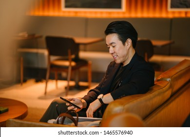 Portrait of a handsome, confident and well-dressed young Chinese Asian man checking his smartphone as he sits on a leather sofa in a well-appointed sofa during the day.