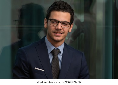 Portrait Of Handsome Confident Young Businessman Standing Arms Crossed