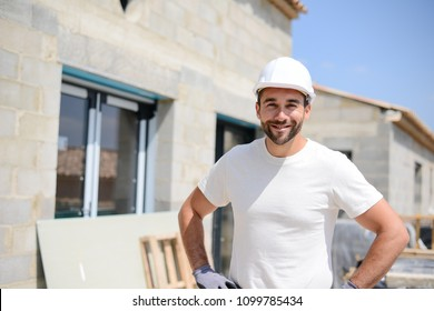 portrait of handsome construction worker on a house building industry construction site