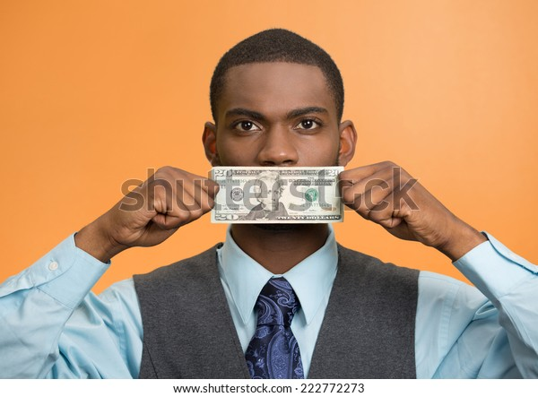 Portrait handsome corrupt guy businessman holding twenty dollar bill to mouth silent avoiding truth isolated orange background. Bribery concept in politics business diplomacy. Face expression attitude