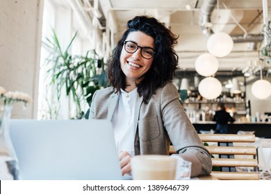 Portrait of handsome curly business woman sitting and working in city cafe with laptop and smiling
