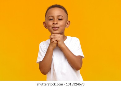 Portrait of handsome cute ten year old African boy making hopeful adorable facial expressions, holding hands clasped under his chin, begging his mother to buy him expensive toy. Hope and innocence