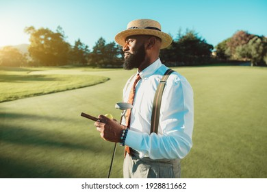 A portrait of a handsome dapper bearded black man in an elegant outfit: white shirt, trousers with suspenders, tie, and hat, is standing on the golf field and holding the club, cigar, and ball in hand