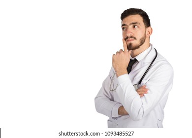 Portrait of a handsome doctor wearing his uniform, standing and he is thinking about something putting his finger on his cheek, isolated on white background