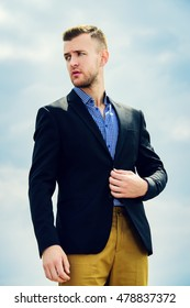 Portrait of a handsome elegant man in a suit over blue sky. Fashion shot. Business man outdoor.