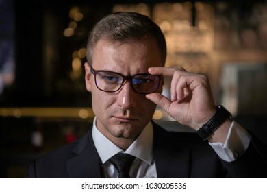Portrait of handsome elegant serious Caucasian businessman looking at camera.