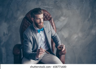 Portrait of handsome elegant young red bearded man holding glass of cognac and a cigar, sitting and resting in a formal wear in leather arm chair, so harsh, sucessful and rich!