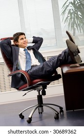 Portrait of handsome employee having rest in arm-chair in office