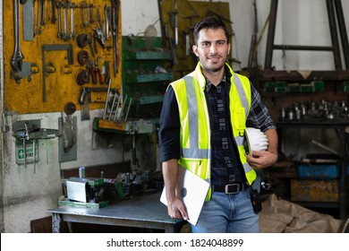portrait handsome engineer man or factory worker holding laptop computer and helmet