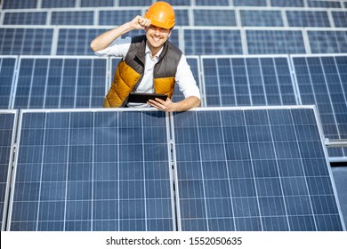 Portrait of a handsome engineer in protective helmet standing with digital tablet on a solar power plant. Solar station development concept