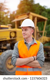 Portrait of handsome engineer is stand with road construction vehicle background.