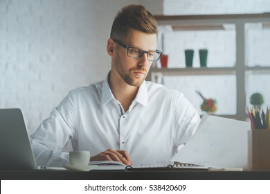 Portrait of handsome european boy with document in hand at workplace