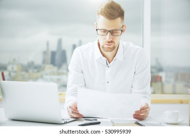 Portrait of handsome european guy with document in hand at workplace