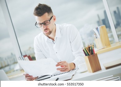 Portrait of handsome european male with document in hand at workplace