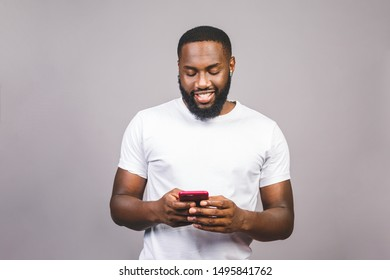 Portrait of handsome excited cheerful joyful delightful curious guy wearing casual sending and getting messages to his lover isolated against grey background. Using phone.