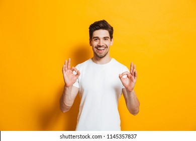 Portrait of handsome excited man in basic clothing smiling and showing ok sign at camera isolated over yellow background