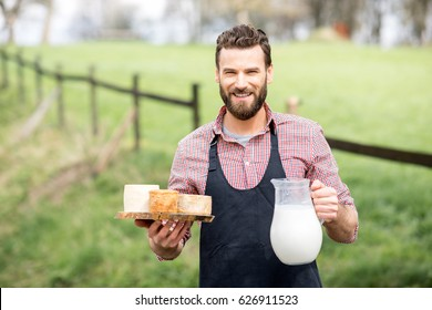 Portrait of a handsome farmer in apron standing with goat cheeses and milk outdoors on the green meadow background