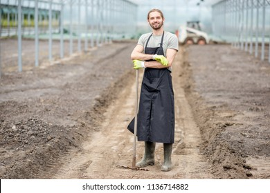 Portrait of a handsome farmer in working uniform standing with rake in the glasshouse