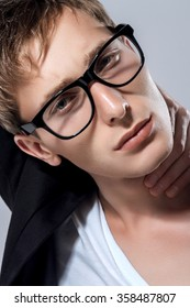 Portrait Of A Handsome Fashion Man In Glasses On Gray Background