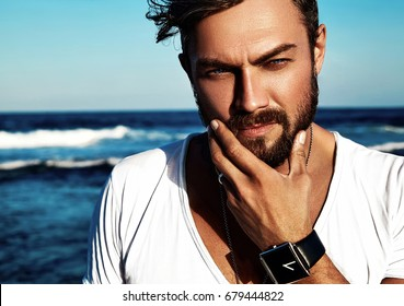 Portrait of handsome fashion man model wearing white clothes posing on blue sea background. Touching his beard