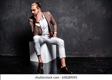 portrait of handsome fashion stylish hipster businessman model dressed in elegant brown suit sitting near dark wall in studio