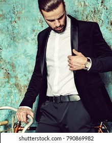 portrait of handsome fashion stylish hipster lumbersexual businessman model dressed in elegant black suit in  posing near sport bicycle and blue grange wall in studio. Metrosexual