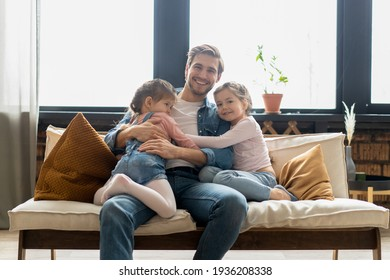 Portrait of handsome father and his cute daughters hugging and smiling.