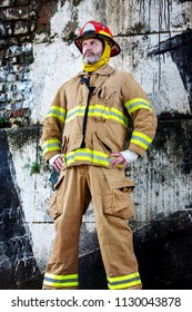 portrait of handsome fireman in uniform standing in front of wall