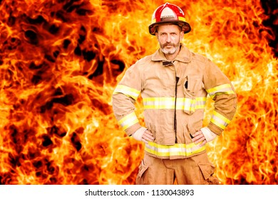 portrait of handsome fireman in uniform standing in front of wall of fire