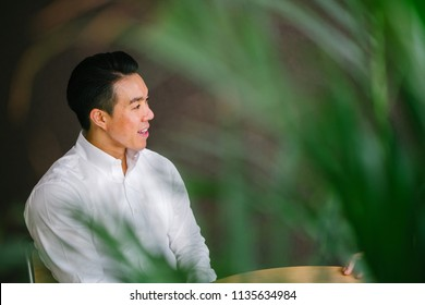 Portrait of a handsome, fit and confident Chinese Asian businessman sitting at a table in a meeting room and having a business discussion (interview) with a person that is out of view.