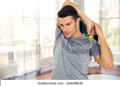 Portrait of a handsome fitness man warming-up at gym