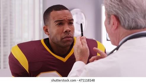 Portrait of handsome football player consulting sports injury with a doctor.