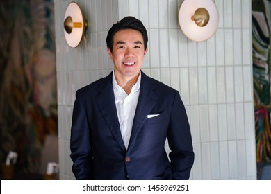 Portrait of a handsome, good looking and attractive Chinese Asian man in a well-tailored suit in a stylish interior. He is tall, athletic and smiling as he poses confidently against a wall.