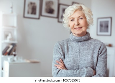 Portrait of handsome grandmother in gray sweater, crossed hands