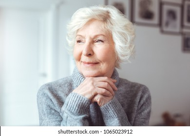 Portrait of handsome grandmother in gray sweater. Dreaming, wondering concept