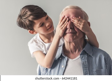 Portrait of handsome grandpa and grandson on gray background. Boy is covering grandpa's eye making a surprise