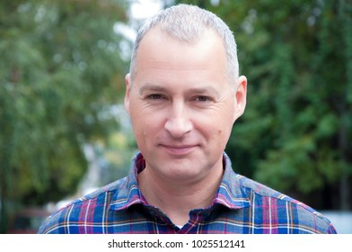 Portrait of handsome grey haired businessman in plaid t-shirt in the street.