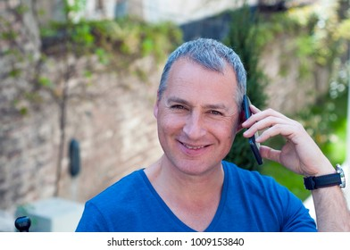 Portrait of a handsome grey haired man in public park talking over the phone