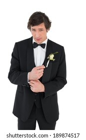 Portrait of handsome groom in tuxedo getting ready over white background