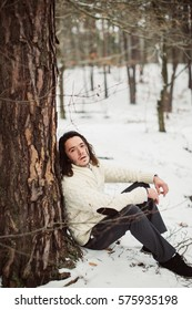 Portrait if handsome groom in the winter park outside