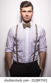 Portrait of a handsome guy with suspenders and bow-tie on gray background.