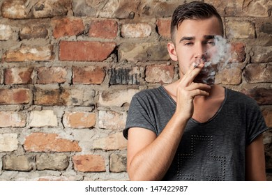 Portrait of a handsome guy who is smoking a cigarette while standing near a brick wall