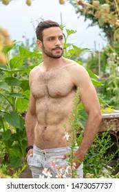 Porträt eines hübschen, haarlosen, im Garten stehenden Mannes