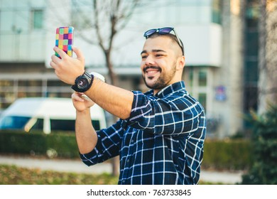 Portrait of a handsome happy man taking a selfie outdoors with his smartphone