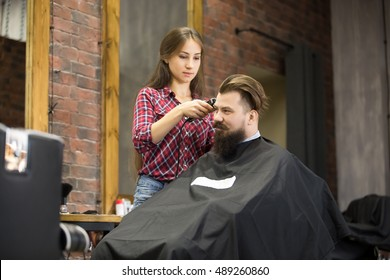 Portrait of handsome happy young bearded caucasian man getting trendy haircut in modern barber shop. Attractive barber girl working, serving client, doing haircut using shaver. Indoors shot