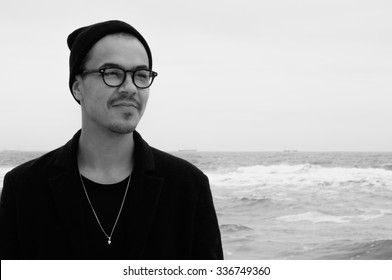 portrait of handsome hipster guy in glasses and hat on hazy cold sea background black and white