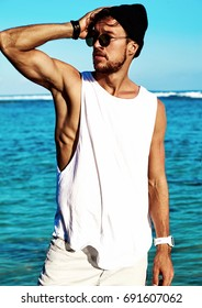 Portrait of handsome hipster sunbathed fashion man model wearing casual clothes in white T-shirt and sunglasses posing on blue ocean and sky background