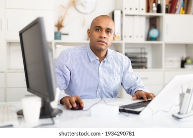 Portrait of handsome hispanic employee looking at camera and sitting at office desk